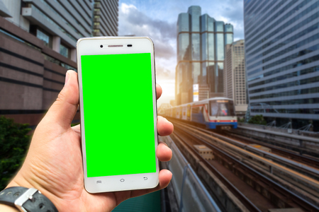 Men use smartphone blurred images in the BTS Skytrain in Bangkok with evening sunset for travel lifestyle transportation concept in the big city. green screen
