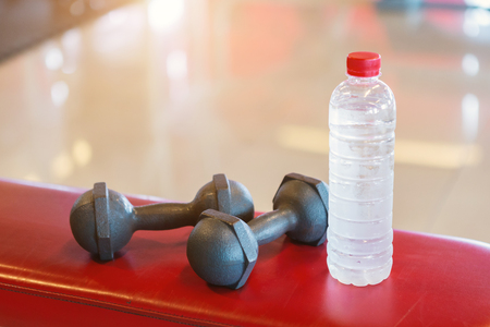 Dumbbells and water on a empty black rubber floor floor in defocused sport gym interior and fitness health club with sports exercise equipment, weight training equipment. Stock fotó