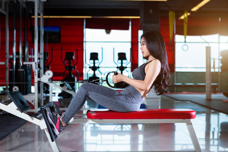 Fitness Asian women performing doing exercises training with rowing machine (Seat Cable Rows Machine) in sport gym interior and fitness health club with sports exercise equipment Gym background