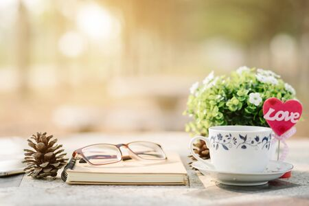 Close-up of empty notebook,spectacles and cup of coffee on Marble floor background. Love concept with heart desktop,Valentine's Day.