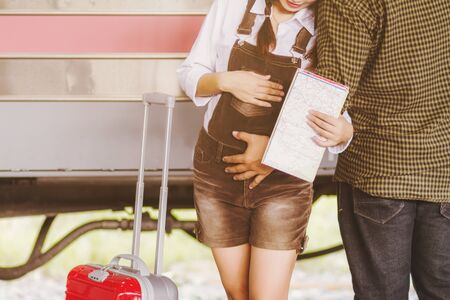 Asian woman pregnant, Couple lovers tourist hugging in at train station. Stock Photo
