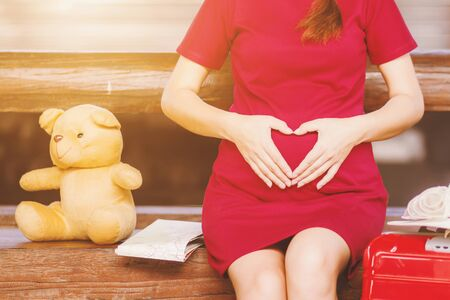 Asian woman pregnant red dress Heart-shaped handmade sitting on a bench with Teddy Bear and map with red suitcase at railway station travel.