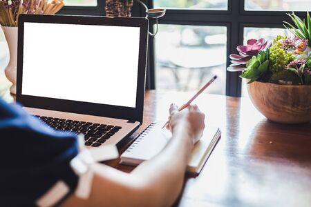 Primer plano de mujer de negocios trabajando con ordenador portátil hacer una nota en la cafetería como el fondo. Foto de archivo