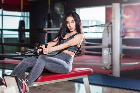 Fitness Asian women performing doing exercises training with rowing machine (Seat Cable Rows Machine) in sport gym interior and fitness health club with sports exercise equipment Gym background.