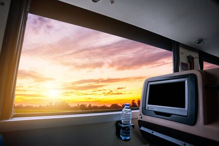 Inside of the bus which has LCD screen blank rear seat for entertainment with a bottle of water and window view of Beautiful landscape nature with sky cloud sunset, Figure tourism road trip concept. Stockfoto