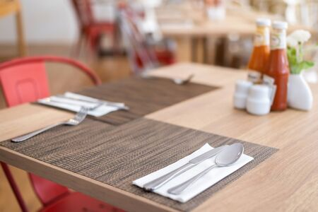 Close-up of luxurious spoon and fork, flower vaseson, sauce bottle the dining table decoration in hotel