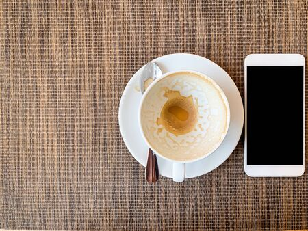 Smartphone and Empty coffee cup on wood desk on top view. Imagens