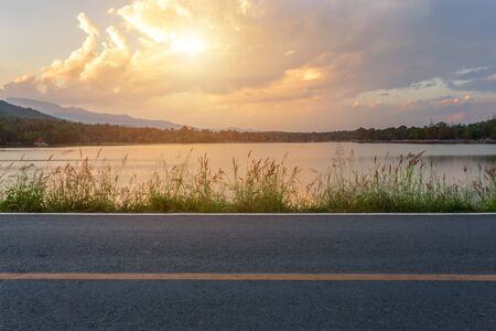 Rural road with Scenic view of the reservoir Huay Tueng Tao with Mountain range forest at evening sunset in Chiang Mai, Thailand