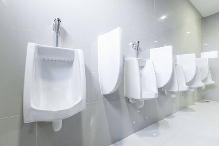 public toilet urinals lined up, no privacy. Stock Photo
