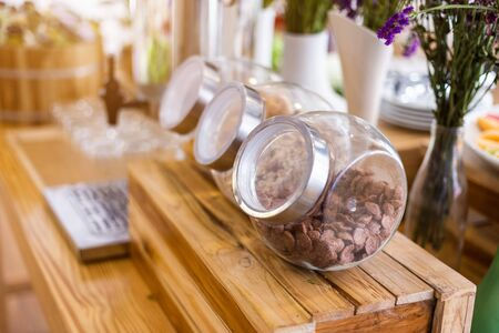 Long row Glass jars with breakfast cereal at on the dining table decoration at buffet self service at hotel. Stok Fotoğraf