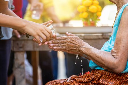 pouring water on the hands of revered elders and ask for blessing happy for the songkran festival in Thailand, Traditional Thailand New Year.