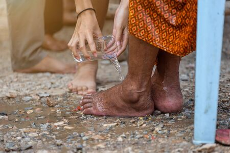 Hand of pouring water on the foot of revered elders and ask for blessing happy for the songkran festival in Thailand, Traditional Thailand New Year.