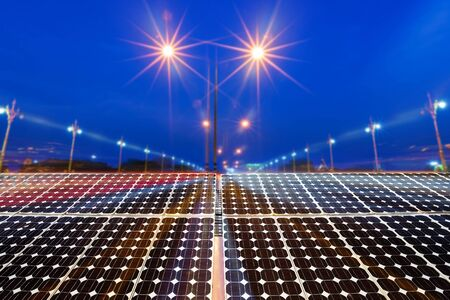 Texture of photovoltaic panels solar panel with city night light on the Road at night background, Alternative energy concept. 免版税图像