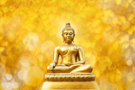 Beautiful of Golden Buddha statue on golden yellow bokeh leaf Pho leaf (Bo leaf) background.