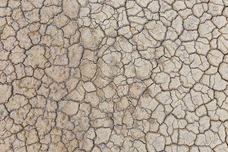 Suelo seco marrón o fondo de textura de tierra agrietada.