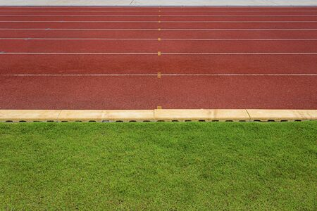 texture of running racetrack red rubber racetracks in outdoor stadium are 8 track and green grass field,empty athletics stadium with track, football field, soccer field.