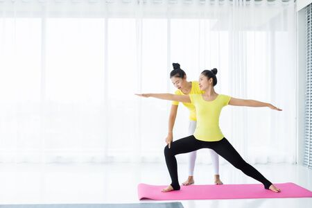Two young Asian women workout practicing yoga in yellow dress or pose with a trainer and practice meditation wellness lifestyle and health fitness concept in a gym.