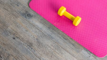 yellow dumbbells on an empty pink rubber floor on wooden floor background,top view with copy space health and exercise concept
