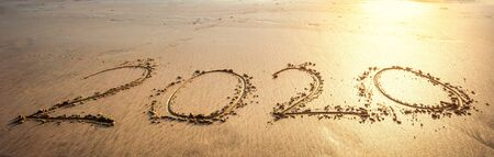Happy New Year 2020 text on beautiful the sea beach with wave early morning sunrise over the horizon background.During Christmas and New Year. Stock Photo