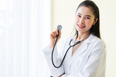 Retrato de la cara sonriente de la joven doctora asiática con estetoscopio en el fondo del hospital. Foto de archivo