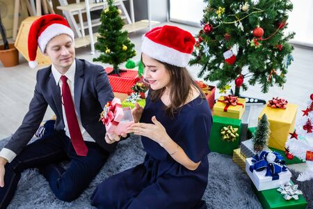 Happy new year 2020 concept,Happy couple holding exchanging gifts and Give a present in Christmas and New Year's Eve party Christmas tree background After finishing business work Stock Photo
