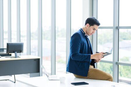 En pensant à un jeune homme d'affaires asiatique travaillant avec la lecture de la note enregistrée dans le cahier de plan d'affaires et l'ordinateur portable, un smartphone est assis sur la table Dans le fond de la salle de bureau.