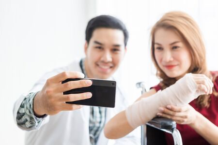 Selfie of smiling man doctor with a female patient wear arm splint for better healing sit in a wheelchair Abstract blur with focus using a smartphone In the room hospital background.