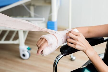 Close-up of a nurse bandages with splint the arm of female patient hand due to with her arm broken for better healing sit in a wheelchair In the room hospital background. Banco de Imagens