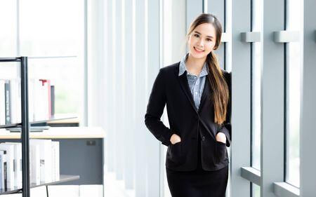 Ritratto di un'allegra donna d'affari asiatica matura in background in ufficio, gli affari hanno espresso fiducia e incoraggiano il concetto di successo
