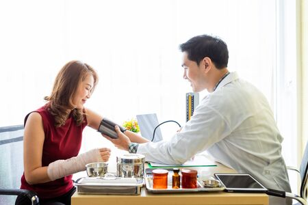 Asian Young man doctor with measuring the pressure to the arm of a female patient wear arm splint with analogue pressure gauge for better healing In the room hospital background. Banco de Imagens