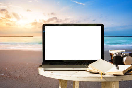 Mockup of laptop computer with empty screen with camera,notebook,coffee cup on table at landscape early sunrise over blue the sea background,working on the beach,Freelance work and holiday traveler.