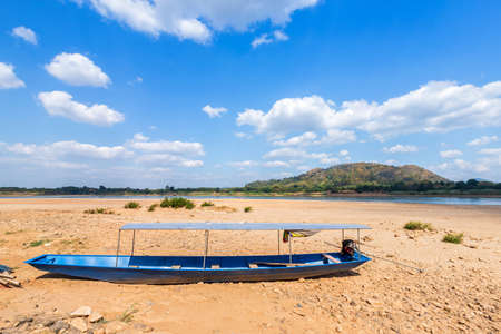 Boat parked in on the dry sand ground of Mae Khong river with Mountain views of Laos at the Kaeng Khud Khu rapids at Chiang Khan in Loei province,Thailand.
