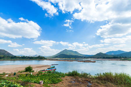 Riverside view of Mae Khong river and the a boat parked in port, Mountain views of Laos at the Kaeng Khud Khu rapids at Chiang Khan in Loei province, Thailand.