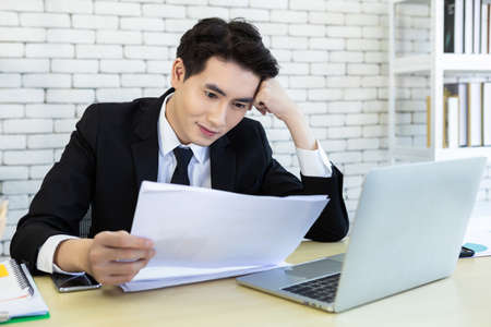Happy of successful asian young businessman have stressed see a the document business plan and laptop computer on wooden table In the office room background.