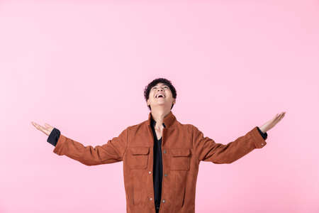 Asian a man handsome young makes scale with arms feels happy and confident in love isolated on pink blank copy space studio background.
