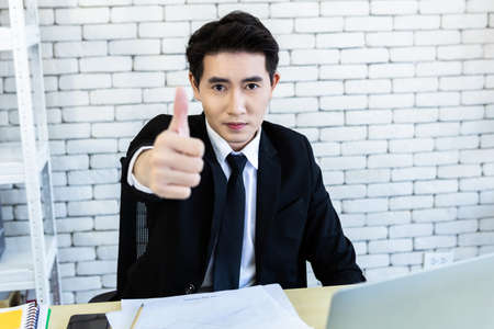 Happy mood a cheerful successful asian young businessman worked with laptop computer positive adult business showing thumbs up and ideas on wooden table background in office