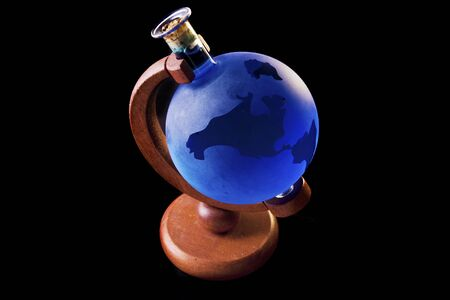 A glass bottle globe, filled with blue liquid, on an old wood axis Stock Photo