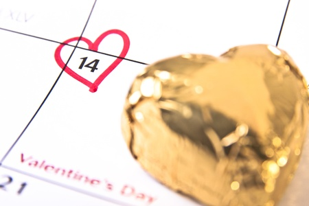 A red heart encircling February 14 on a calendar and a heart-shaped chocolate wrapped in gold foil.