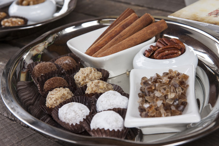 A plate of handmade chocolate truffles with cinnamon, pecans, and salt crystals Stock Photo