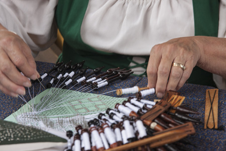 A woman demonstrates the traditional way to make lace using bobbins