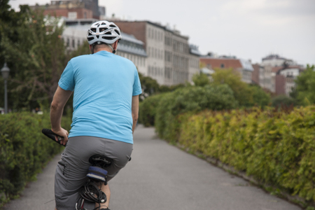 A man rides on a bicycle down a city path Stock Photo