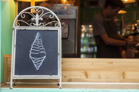 A chalkboard sign showing an ice-cream cone in a shop window