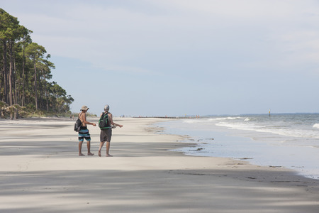 Two teenage male tourists strolling on a beach in South Carolina