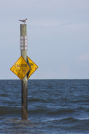 A sign at the beach warning about the water level
