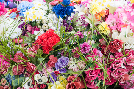 Colorful artificial flower mixture of different varieties as background.