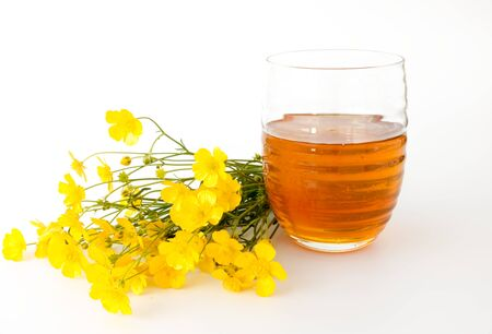 orange blossom: Orange Blossom honey in a glass surrounded by wild yellow flowers. Isolated on white background.