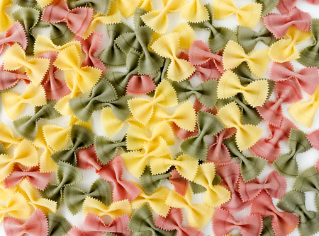 extra large: Extra large multicolored farfalle pasta spread out on a white background.