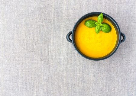 positioned: Brown ceramic bowl with handles, filled with butternut squash soup on grey linen background. Positioned in top right corner for lots of copy space on grey linen background.
