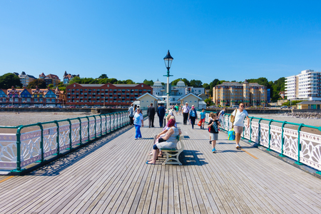 day trip: Penarth, United Kingdom - August 15, 2016: Tourists, locals and families are walking towards the end of the Victorian Penarth Pier to catch the Balmoral ship which is about to leave for a day trip. Editorial