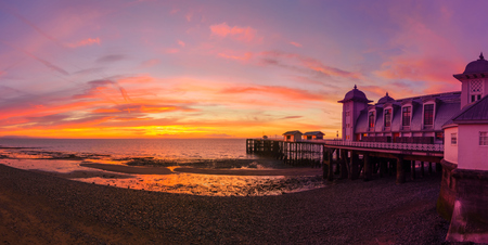 Dramatic sky in yellow, red and magenta colors and Penarth Pier before sunrise. Panorama image. Editorial